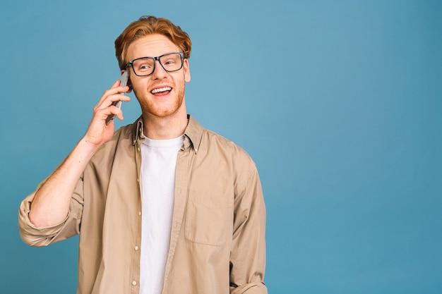 Ah bonne nouvelle ! souriant jeune homme décontracté parlant au téléphone mobile