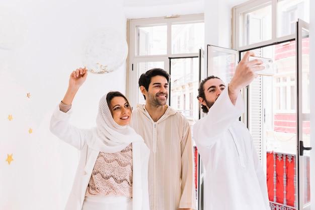 Aïd concept avec un groupe d'amis prenant selfie