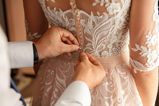 Aide au mariage dans la cabine d'essayage. mains du marié sur la robe de mariée. heureux mariage et mariée au concept du jour du mariage