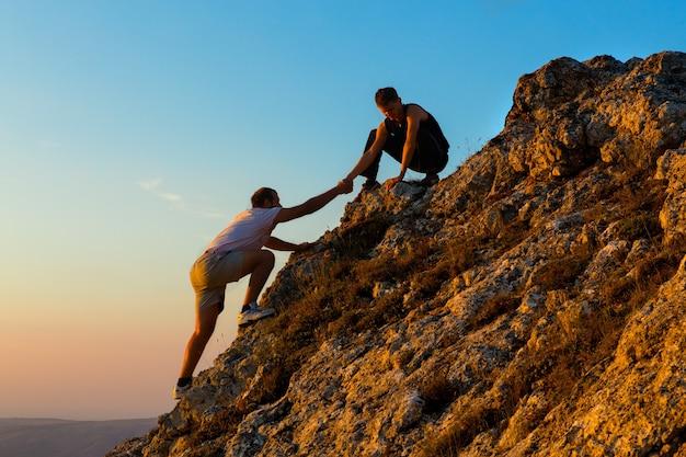 Aide au travail d'équipe défi d'escalade de montagne aube lever du soleil