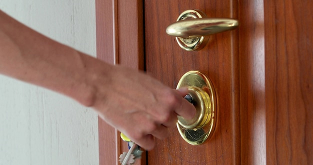 À l'aide d'une clé pour ouvrir la serrure de la porte d'entrée