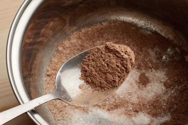 À l'aide d'une cuillère, recouvrir de cacao de sucre et de cacao. ajout de cacao dans le bol