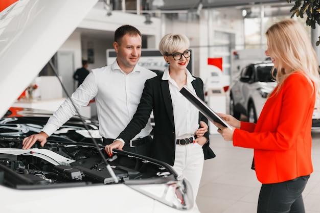 Aide du concessionnaire pour couple choisit une voiture chez le concessionnaire.
