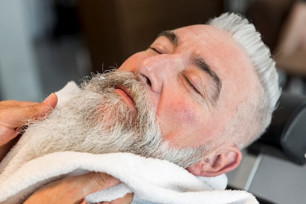 À l'aide d'une serviette sur la barbe d'un homme âgé dans le salon de coiffure