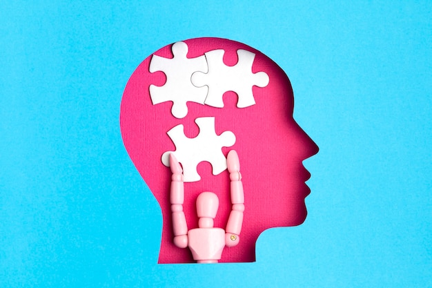 Aide avec la tête de papercut concept maladie mentale avec des pièces de puzzle à l'intérieur