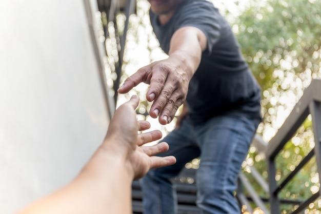Aider les mains de concept à tendre la main pour s'entraider sur fond de bokeh