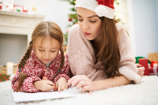 Aider la petite fille avec la décoration de noël