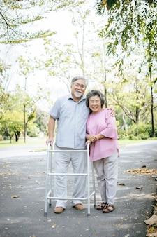 Aider son patient senior qui utilise un déambulateur pour le soutien
