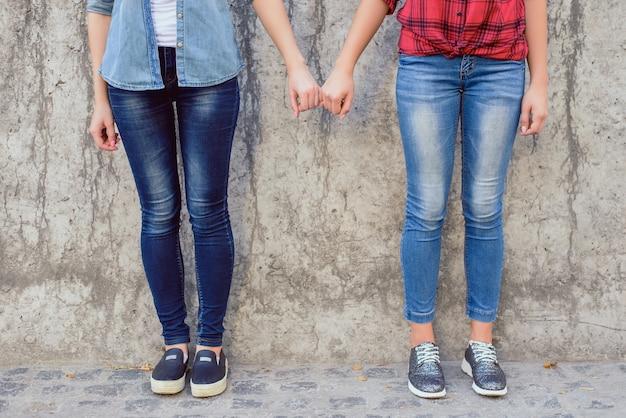 Aidez les lesbiennes à réconforter le concept de console. la photo en gros plan de deux jolies filles d'âge adolescentes adorables tenant des petits doigts portant des jeans élégants isolés sur la surface d'un mur gris en béton