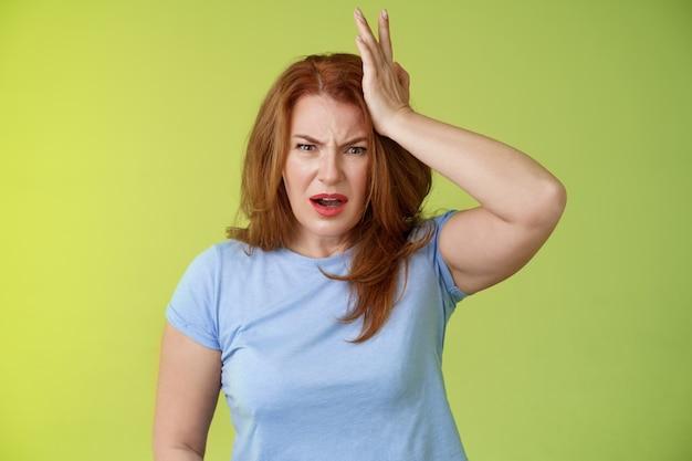 Aïe vous donnez un coup de pied dans la tête frustré inquiet bouleversé femme rousse moyenne regard choqué en détresse touch temple se plaindre enfant tirer balle son visage se tenir déçu mur vert