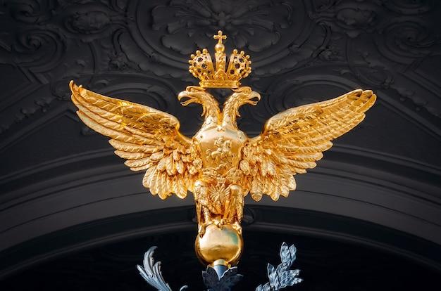 Aigle à deux têtes brillant doré sur fond sombre.