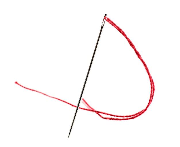 Aiguille à coudre avec fil sur blanc