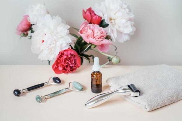 Aiguille derma roller, rouleaux de massage jade guasha et flacon de sérum avec fleurs de pivoine en arrière-plan, microneedling à domicile et soins de la peau