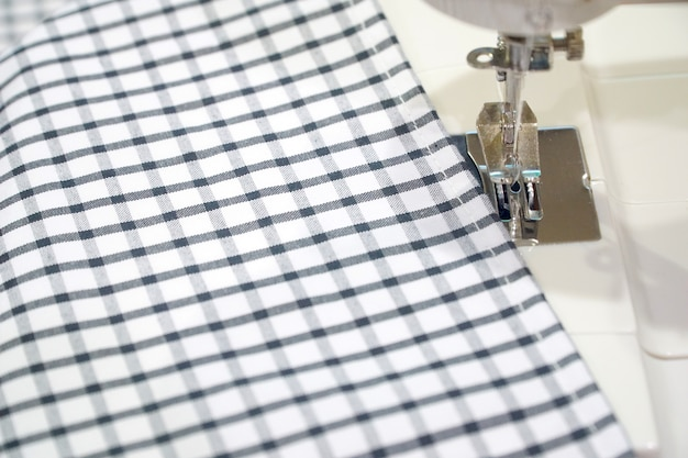 Aiguille et machine à coudre avec tartan en tissu noir et blanc.