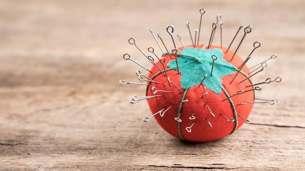 Aiguilles à coudre dans un coussin de tomate