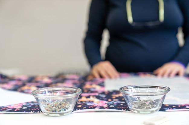 Aiguilles dans un bol sur une table de couture dans un atelier de couture