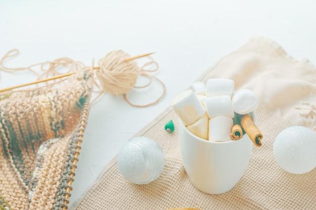 Aiguilles de foulard tricotées et pelote de laine chocolat chaud avec guimauves et nappe cannelle sur un ...
