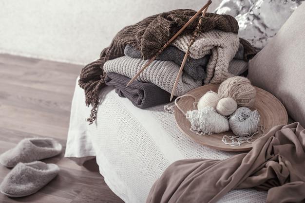 Aiguilles à tricoter en bois vintage et fils sur un canapé confortable avec des oreillers et des pantoufles à proximité