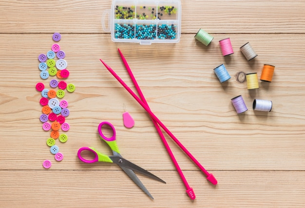 Des aiguilles à tricoter; bouton; bobine; perles et ciseaux sur planche de bois