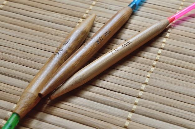 Aiguilles à tricoter circulaires en bambou sur une surface en bois.