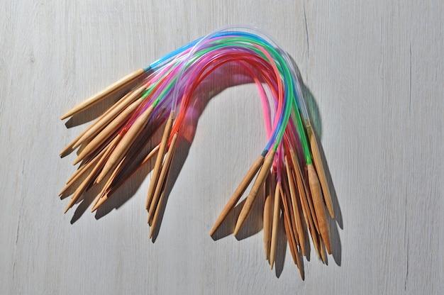 Des aiguilles à tricoter circulaires reposent sur le comptoir