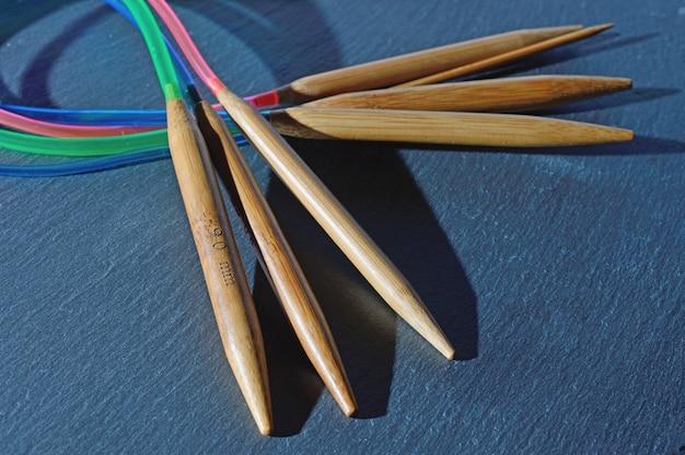 Les aiguilles à tricoter circulaires reposent sur une surface texturée noire.