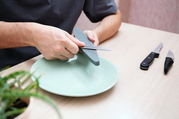 Aiguiser le couteau avec la pierre à aiguiser. entretien des appareils de cuisine.