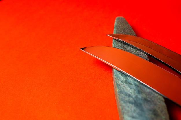 Aiguiseur de couteaux et pierre pour aiguiser les couteaux sur rouge.