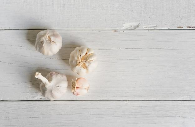 Ail biologique entier et clous de girofle sur fond de bois blanc.