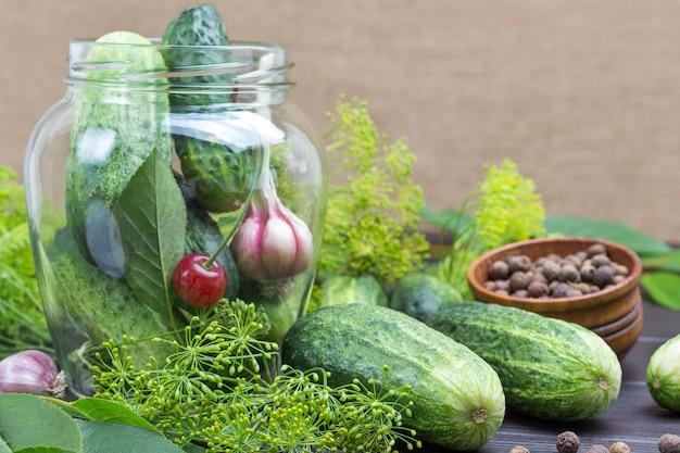 Ail, concombres et cerises dans un bocal en verre. concombres et aneth sur table. produits de fermentation faits maison