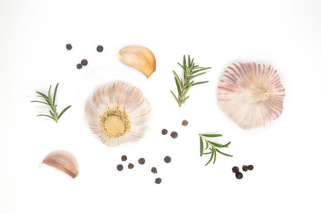 Ail entier cru bio, poivre noir et romarin frais sur fond isolé blanc en vue de dessus à plat.