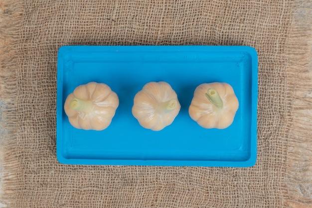 L'ail fermenté fait maison sur plaque bleue avec de la toile de jute