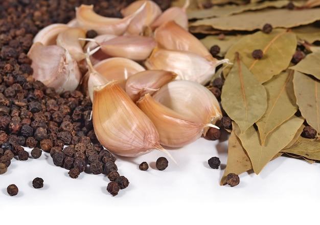 Ail, feuilles de laurier et grains de poivre sur fond blanc