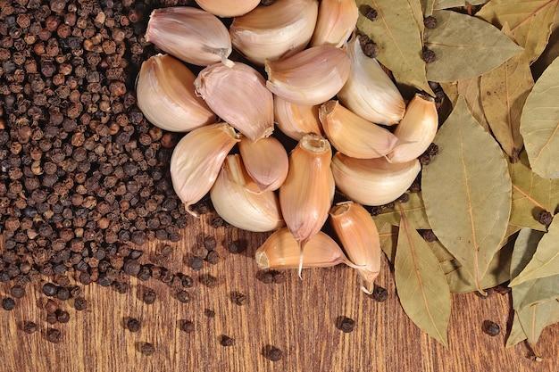 Ail, feuilles de laurier et grains de poivre sur un fond en bois