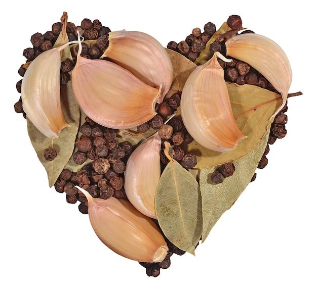 Ail, feuilles de laurier et grains de poivre en forme de coeur sur fond blanc