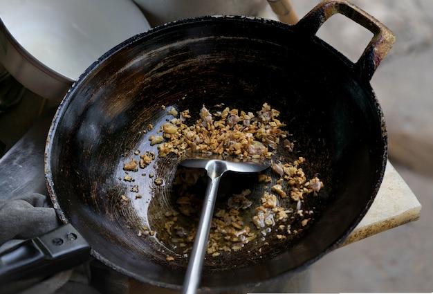 Ail frit dans une casserole en métal noir avec une louche dans une cuisine chinoise