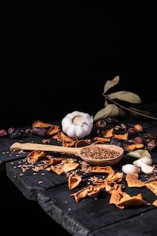 Ail, fruits secs et graines en surface rustique sombre. photo artistique d'ail et de fruits secs sur une vieille table noire tourné en style ciaroscurro discret