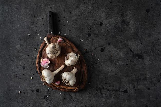 Ail naturel frais sur une planche à découper avec du sel de mer et du poivre noir sur une pierre noire foncée