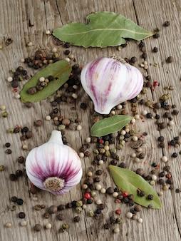 Ail, poivre et feuilles de laurier sur table en bois