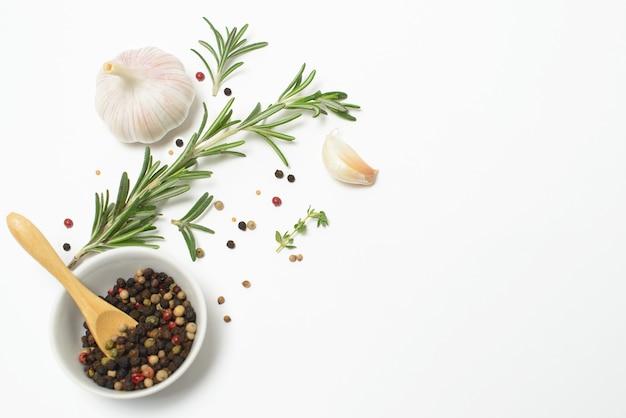 Ail, romarin, feuilles de laurier, piment de la jamaïque et poivre isolé sur un espace blanc. mise à plat. vue de dessus