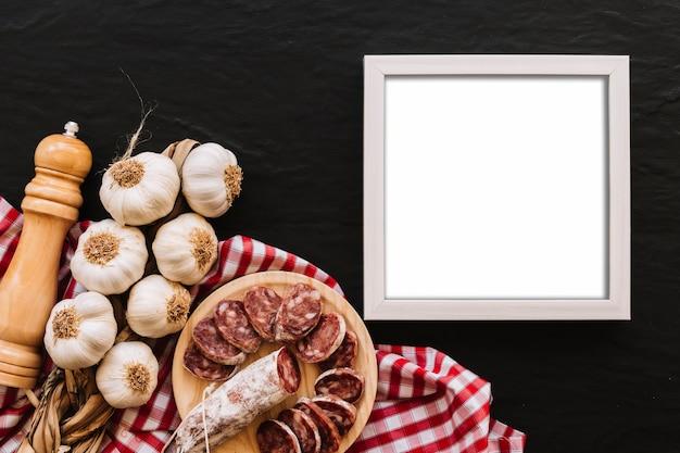 Ail et saucisse près des épices et du cadre vide