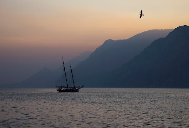 Ailboat voile au coucher du soleil sur l'arrière-plan d'une chaîne de montagnes