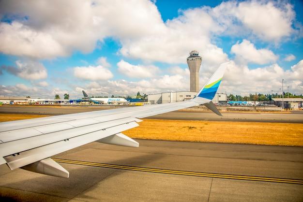 Aile d'avion à un aéroport pendant qu'un avion décolle en alaska