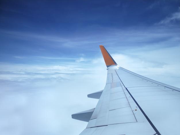 Aile d'avion sur un ciel bleu et des nuages blancs, vue depuis la fenêtre pendant le vol