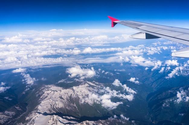 Aile d'un avion volant au-dessus de beaux nuages