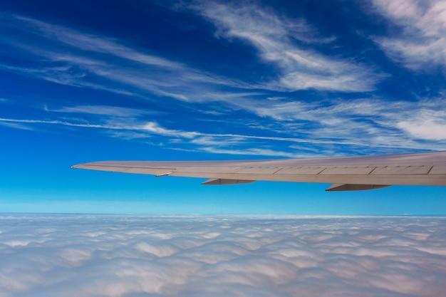 Aile d'avion volant au-dessus des nuages dans le ciel