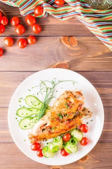 Aile de dinde au four, tranches de concombre et tomates cerises sur une plaque sur une table en bois. vue de dessus