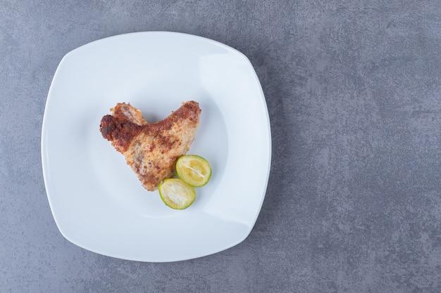 Aile frite croustillante sur plaque blanche.