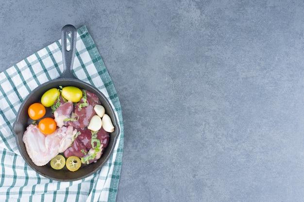Aile de poulet cru et légumes frais sur une poêle noire.
