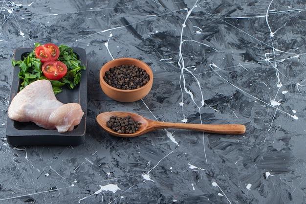Aile de poulet et légumes sur une planche à côté d'un bol d'épices et d'une cuillère, sur fond de marbre.